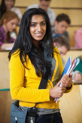 Student smiling at camera in front of her class in lecture hall