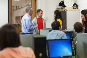 Students speaking with their teacher in computer room
