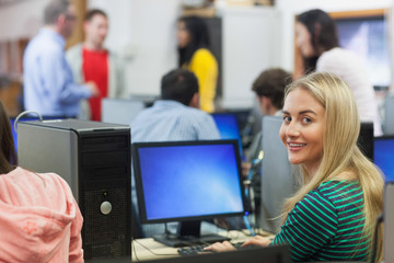 Blonde student smiling at camera in computer room