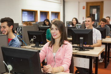 Smiling students listening in their computer class