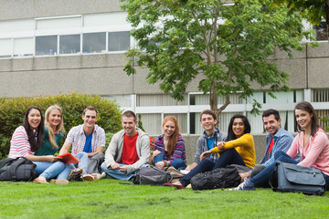 Group of students smiling at camera on the grass on campus