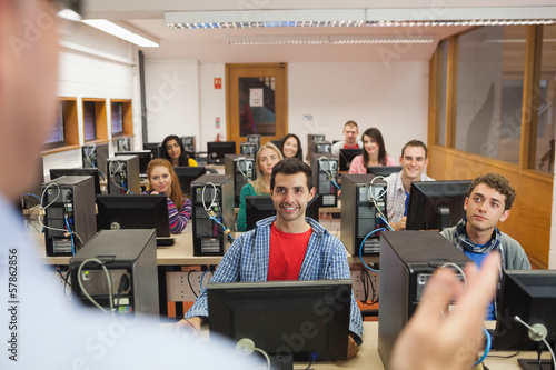 Cheerful students listening to lecturer in their computer class
