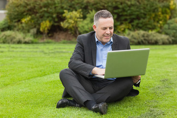 Smiling lecturer sitting outside on campus using his laptop