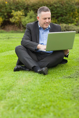 Happy lecturer sitting outside on campus using his laptop