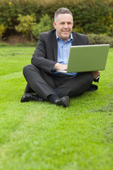 Happy lecturer sitting outside on campus using his laptop looking at camera