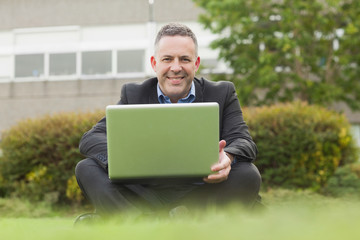 Smiling professor sitting outside on campus using his laptop looking at camera