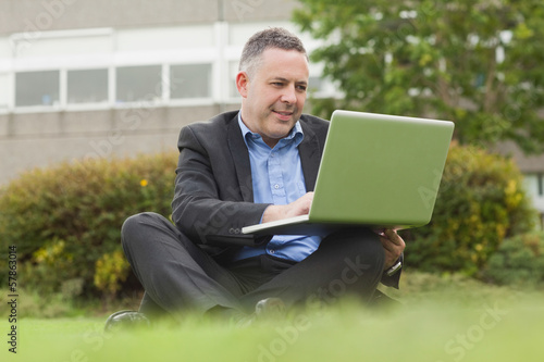Smiling professor sitting outside on campus using his laptop