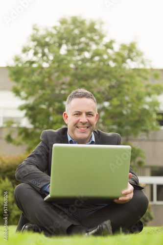 Happy professor sitting outside on campus using his laptop looking at camera
