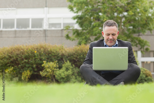 Happy professor sitting outside on campus using his laptop