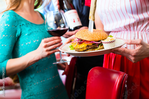 People in American diner with burger and wine