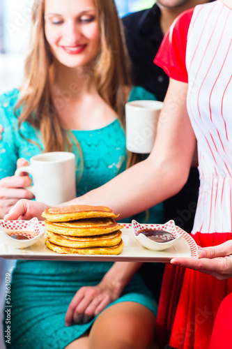 People in diner or restaurant having pancakes