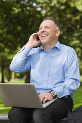 Laughing professor talking on phone while sitting on bench using laptop on campus