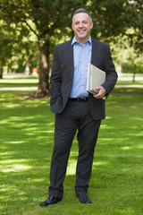 Smiling professor standing on campus holding notepads