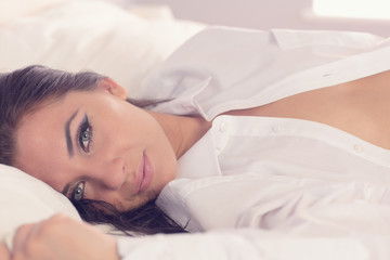 Lovely calm woman lying on her bed wearing a white shirt