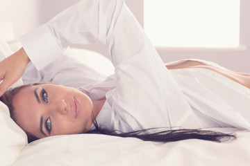 Attractive woman stretching out in her bed wearing a white shirt