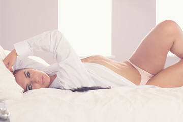Attractive woman stretching out on her bed looking at camera