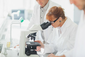 Woman standing looking through microscope