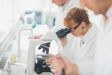 Female scientist wearing a lab coat looking through a microscope