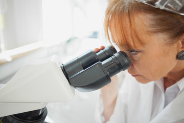 Close up of female scientist looking through a microscope