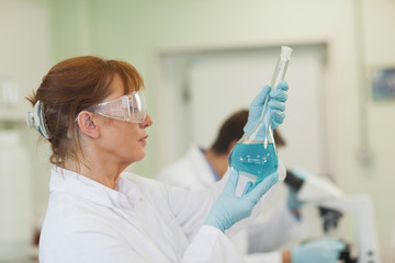 Profile view of female scientist holding an erlenmeyer flask