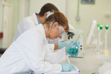 Female scientist leaning on a desk writing on a clipboard