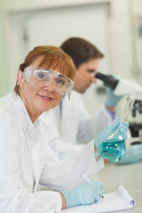 Cheerful female scientist standing in a laboratory while writing