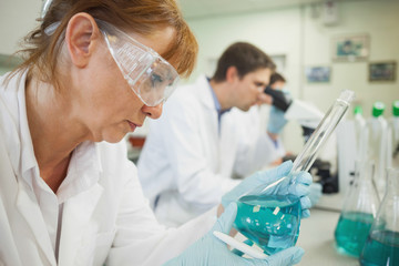 Mature female scientist looking at an erlenmeyer flask