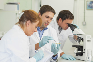Three scientists standing in a laboratory