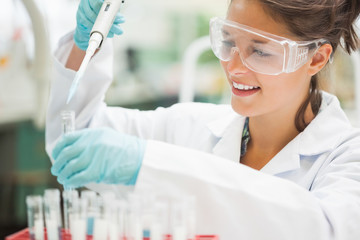 Attractive smiling student holding big pipette