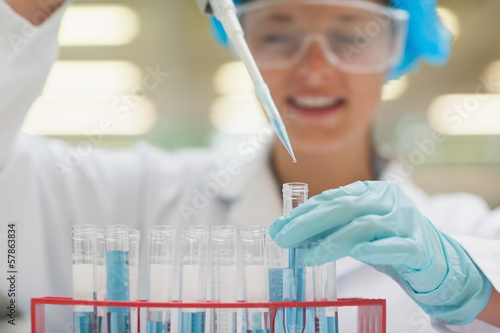 Smiling student using pipette holding test tube