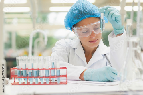 Student holding test tube and taking notes