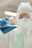 Lab assistant with mask pouring blue liquid in beaker