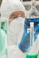 Lab assistant with mask looking at blue liquid