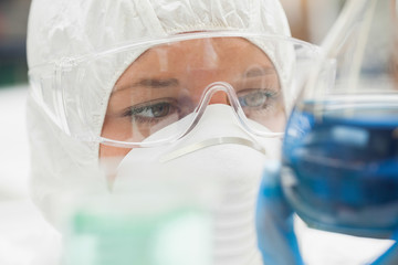 Lab assistant with mask looking closely at blue liquid