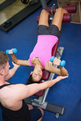 Trainer correcting sporty brunette exercising with dumbbells