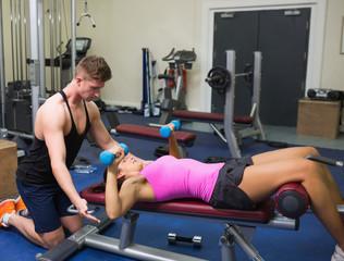 Trainer correcting brunette exercising with dumbbells