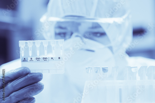 Lab assistant with mask looking closely at test results