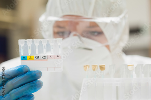 Lab assistant with mask looking at test results
