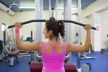 Toned woman exercising on weight machine