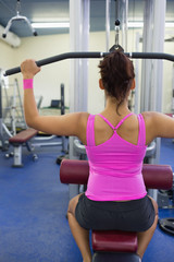 Fit woman exercising on weight machine