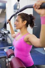 Calm woman exercising on weight machine