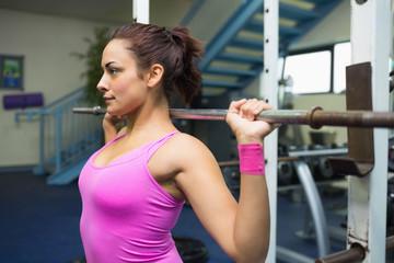 Serious brunette holding barbell