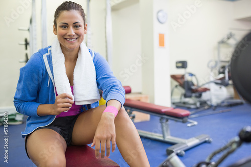 Smiling sporty brunette sitting on bench