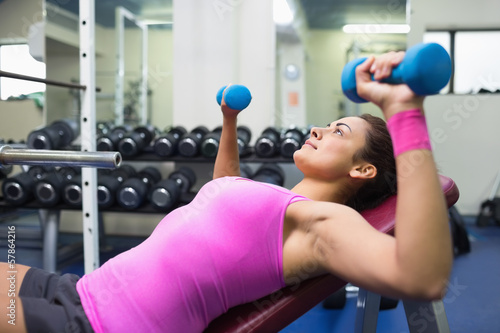 Sporty brunette lying on bench working out with dumbbells