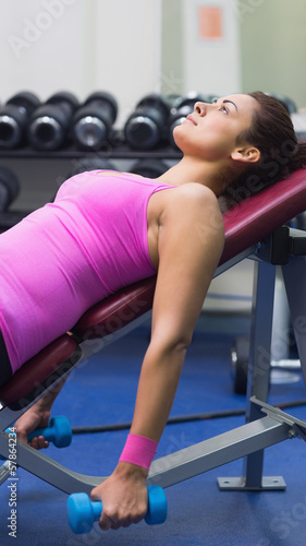 Focused brunette lying on bench holding dumbbells