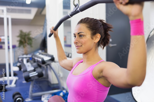 Content woman exercising on weight machine