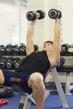 Muscular man lying on bench training with dumbbells