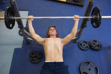 Muscular good looking man lying on bench lifting barbell