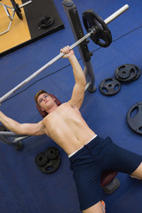 Man lying on bench lifting barbell