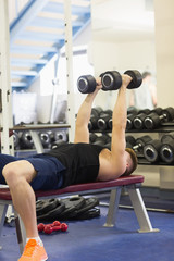Muscular attractive man lying on bench holding dumbbells